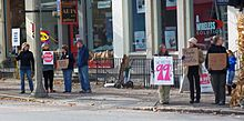 "A group of seven people holding hand-lettered cardboard signs along a city street. The largest says ""We are the 99%"""