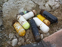 A pile of rejected and somewhat rusty scuba cylinders lying in a yard