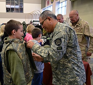 Oregon State Defense Force - Staff Sgt. (ORSDF) Pedro Toledo (right), with the Oregon State Defense Force, helps a child try on body armor soldiers typically wear for training and deployments.