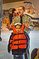 Park Ranger Jonathan Friedman demonstrates the fit of a life jacket on a young visitor, 2016.jpg