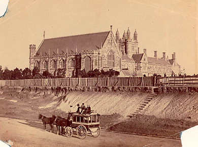 An old sepia photograph shows Sydney University from the west. Only the front section and Great Hall of the Main Building exists. It is separated from the road by a paling fence and a steep eroded incline, where there is now a garden. A horse-drawn bus with passengers up-top is standing in the road.
