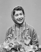 youngish woman in headscarf, smiling towards the camera