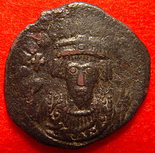 A copper coin with the bust of Phocas. His eyes form the central focus of the image
