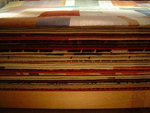 Pile of rugs, shop window, West London, UK in ...