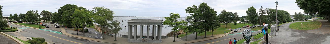 Plymouth Harbor with the Mayflower (left, behind trees), Plymouth Rock (middle) and Cole's Hill (right) with the Statue of Massasoit