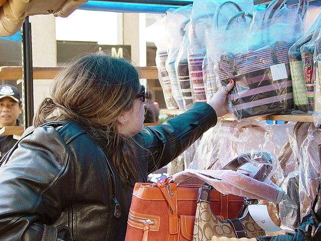 kobieta oglądająca torebki