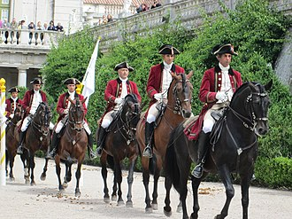 "Lusitano riders of the Portuguese School of Equestrian Art, one of the ""Big Four"" most prestigious riding academies in the world, alongside the Cadre Noir, the Spanish Riding School, and the Royal Andalusian School. . Queluz Palace horses approach (9180978620).jpg"