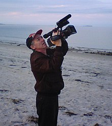 Photograph of Richard Dindo with camera, on beach at Plymouth, Massachusetts, USA, while directing the film Mars Dreamers.
