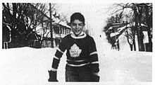 A young boy stands on a snow-covered street. He is wearing a dark-coloured sweater with a stylized maple leaf logo on the chest.