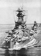 Royal Oak sailing in line astern ahead of two other battleships. R O is painted in very large letters on the top of her B turret.