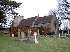 Grey stone building with red tiled roof, partially obscured by a hedge. A square tower is at the far end. The foreground includes several crosses and gravestones.
