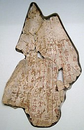Photograph of bone fragment with carved characters