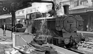 A pannier tank locomotive is standing at a station platform and taking on water from a large filling pipe. The fireman is standing on the locomotive. The driver is controlling the water valve, but may have been distracted by the photographer, as water is cascading over the side of the locomotive. A boy watches.