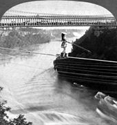 A woman is crossing on a rope over a river.  She wears a wide-brim hat and holds a pole to balance herself while her feet are in buckets.  A double-deck bridge, filled with audience on the lower deck, is in the background.