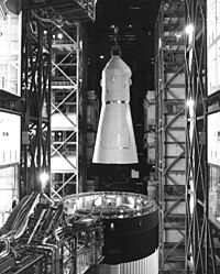 Black-and-white picture from inside a tall building with a space capsule being lifted from the top of a rocket