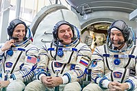 Soyuz MS-11 backup crew in front of the Soyuz spacecraft mockup.jpg