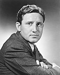 Black and white publicity photo of Spencer Tracy--a middle-aged white man with short curly hairstyle combed to the side and a square face, wearing a suit, in 1935.