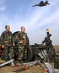 Staff Sgts. Todd Pederson and Robert Roe wait near the flightline as an F-15 Eagle flies overhead during Cope India 2004.jpg