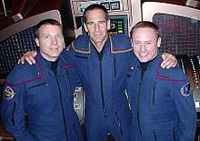 Three men in blue jumpsuits are arm in arm.