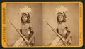 Studio portrait of Hesh-pid-die with feather headress and holding a rifle, by H. Buehman.png
