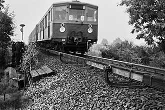 Deutsche Reichsbahn (East Germany) - In 1969 a third-rail S-Bahn train eases past West Berlin firemen fighting a trackside fire in untrimmed brush.