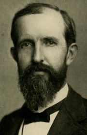 cropped shoulder high portrait wearing a suit and tie, mustache and short beard