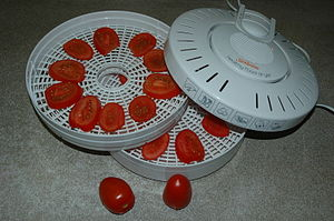 Food dehydrator - Tomato slices ready to be dried in a food dehydrator. In this model, multiple trays can be stacked on top of each other and warm air flows around the food.