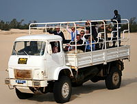 A military-type light truck, originally used for troop transport, and now for safari trips