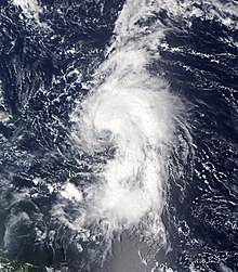 Satellite image of a tropical cyclone in open water. Cloud activity stretches three-fourths the way around the cyclone, and the center is partially exposed.