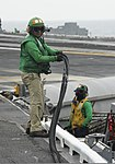 U.S. Navy Chief Aviation Boatswain's Mate (Equipment) Braulio Galvan, left, moves a rubber catapult gasket off the flight deck of the aircraft carrier USS Nimitz (CVN 68) June 13, 2013, while operating 130613-N-ZG290-182.jpg