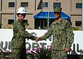 U.S. Navy Ensign Mallory Smith, left, officer in charge of the Diego Garcia detachment, Naval Mobile Construction Battalion (NMCB) 3, shakes hands with Ensign Raymond Bendt, officer in charge of the Diego Garcia 130811-N-ZZ000-010.jpg