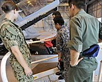 U.S. Navy Lt. Laura Combs, left, an electronic warfare officer assigned to Electronic Attack Squadron (VAQ) 132, discusses the EA-18G Growler aircraft to members of the Japan Air Self Defense Force's Northern 120823-N-VZ328-055.jpg