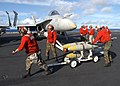 US Navy 030116-N-6895M-509 Aviation Ordnancemen assigned to the Hunters load bombs under the wing of a F-A-18.jpg