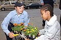 US Navy 040528-N-8238D-024 Gunner's Mate 3rd Class Alicia M. Wulf, of Anaheim, Calif., helps a student from Brooklyn's Crown Heights Youth Collective plant flowers in Public School 242 in Brooklyn.jpg