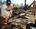 US Navy 051019-N-3729H-257 U.S. Navy Draftsman 2nd Class Robert Smith, assigned to the Nimitz-class aircraft carrier USS John C. Stennis (CVN 74), prepares to cut into a destroyed house with a chainsaw.jpg