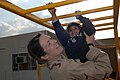 US Navy 070116-N-8218W-089 U.S. Air Force 1st Lt. Lea Ann Fracasso assigned to Wright-Patterson Air Force Base in Ohio, helps an Iraqi girl cross the monkey bars on the play ground at the Civilian Military Operations Center (CM.jpg