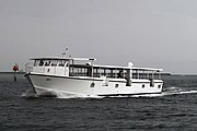 a white ferry boat sails across dark blue waters