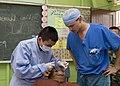 US Navy 090624-N-1722M-674 Malaysian Army Dentist Capt. Chan Ichizensg examines a patient at Seberan Tayor Primary School as U.S. Navy dentist Lt. Brant Cullen looks.jpg