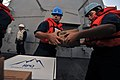 US Navy 110909-N-YZ751-103 Sonar Technician (Surface) 2nd Class Carlos W. Vidal, right, passes a box to Information Systems Technician 2nd Class Ja.jpg
