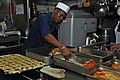 US Navy 111124-N-ER662-039 Culinary Specialist Seaman Odayne Samuels removes turkeys from an oven tray in preparation to be sliced and served for T.jpg
