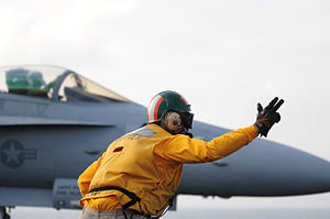 US Navy 111231-N-GZ832-247 Lt. Blake Whetstone, assigned to the air department aboard the aircraft carrier USS Carl Vinson (CVN 70), signals for th.jpg