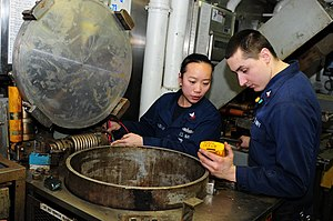 US Navy 120130-N-XP477-158 Electrician's Mate 2nd Class Ratsamy Sophabmixay and Engineman 3rd Class Joshua Hernandez troubleshoot a recycling trash.jpg