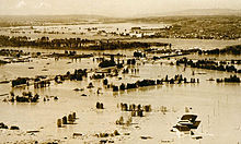 Floodwaters inundate a populated area. A few roadways and partly submerged buildings are visible in the midst of the flood. A long bridge crosses a flooding river in the distance. Beyond the river the ground rises, and buildings there appear to be above water.