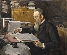 A man with dark gray hair, glasses and a long beard seated at a desk, looking at a music manuscript