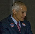 Wesley Clark wearing buttons for Charlie Brown's congressional and Rick Noriega's senatorial campaigns at Netroots Nation 2008 (2680168961).jpg