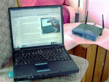Laptop computer and typical home wireless router (right) connecting it to the Internet Wireless network.jpg