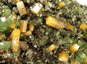Butterscotch-colored wulfenite crystals (lairgest 8mm.) wi green mimetite, frae Ojuela Mine near Mapimi.