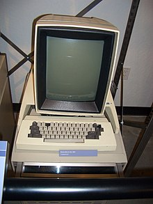 A beige, boxy computer with a small black and white screen showing a window and desktop with icons
