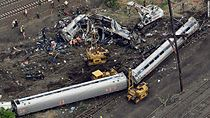 Aerial view of two intact passenger cars resting on their side and one passenger car warped and split open