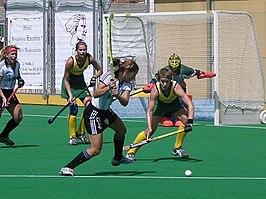 De speelster probeert de bal langs de doelvrouw en een verdedigster te slaan.
